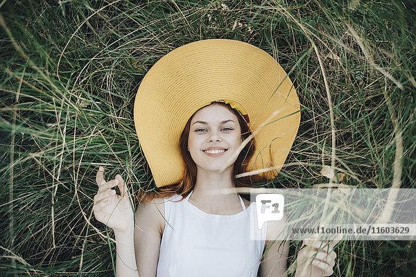 Caucasian woman wearing hat laying in grass