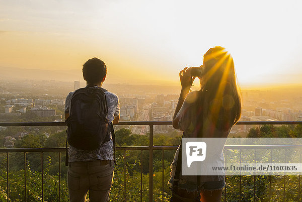 Caucasian couple photographing scenic view of cityscape