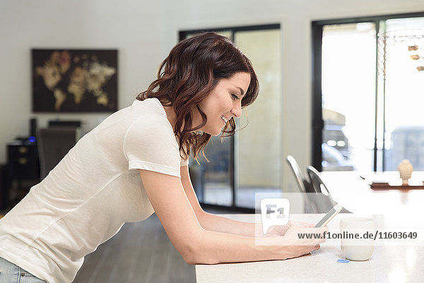 Caucasian woman leaning on table texting on cell phone