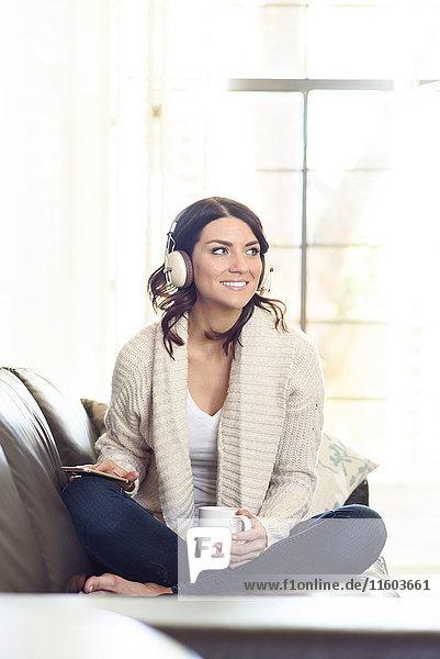 Caucasian woman sitting on sofa listening to headphones