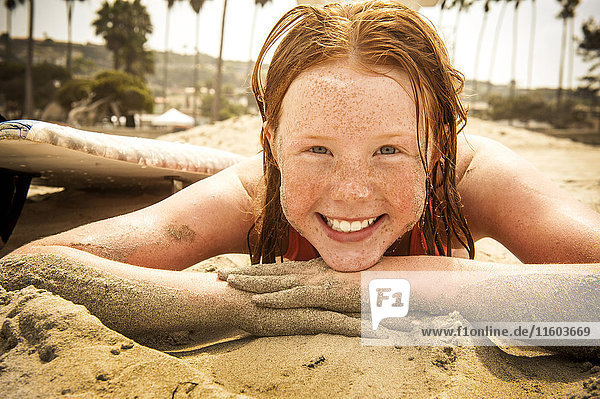 Portrait of smiling girl laying on beach covered with sand