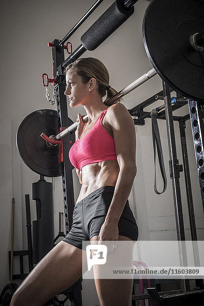 Woman leaning on barbell in gymnasium
