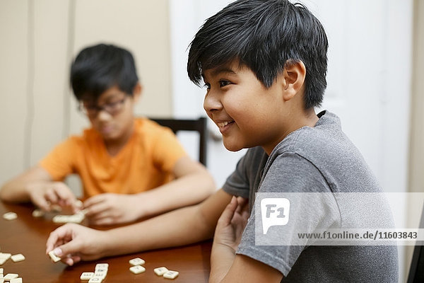 Native American boys playing spelling game at table