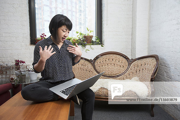 Asian woman video chatting on laptop