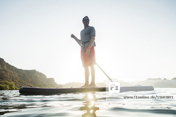 Smiling Hispanic man standing on paddleboard in river