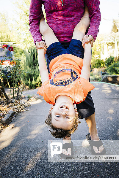 Caucasian mother holding son upside-down