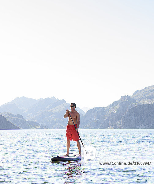Hispanic man on paddleboard in river