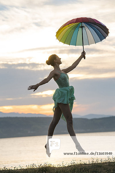 Caucasian ballerina jumping with multicolor umbrella on beach