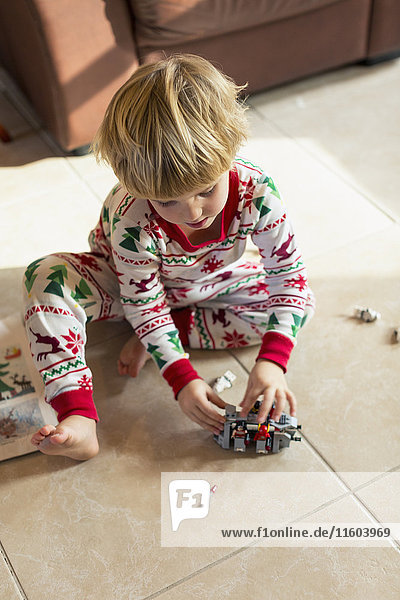 Caucasian boy sitting on floor in pajamas playing with toys