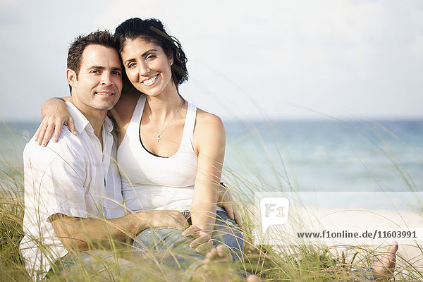 Portrait of Mixed Race couple sitting in grass at beach