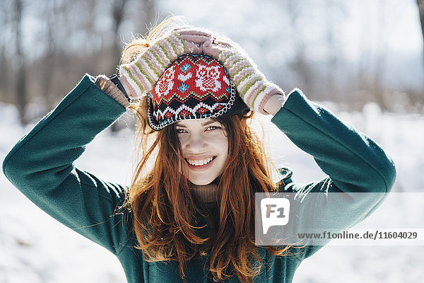 Caucasian woman holding hat on head in winter