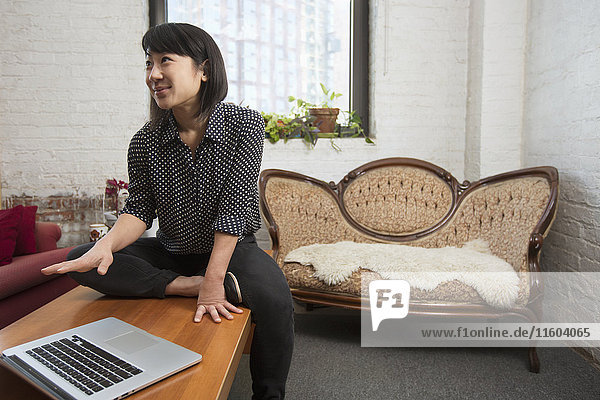 Asian woman gesturing near laptop