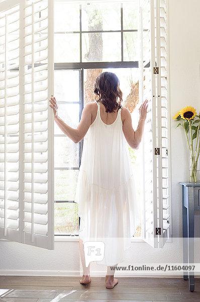 Caucasian woman wearing nightgown opening window shutters