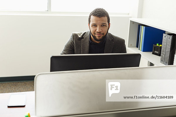Smiling Mixed Race man using computer in office
