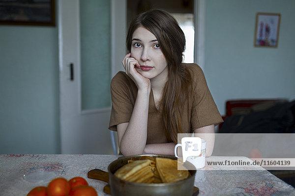Pensive Caucasian woman sitting at table