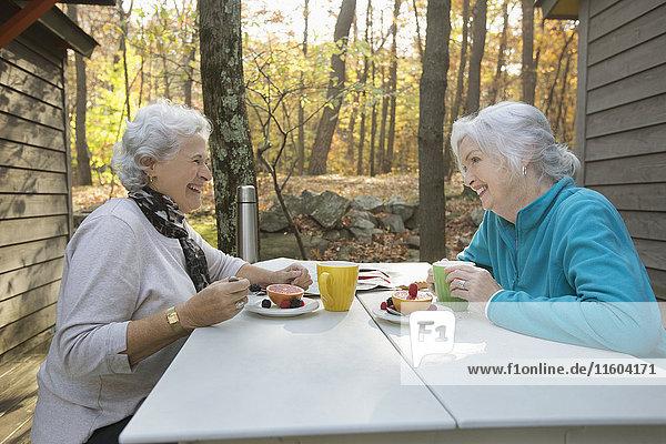 Caucasian women enjoying breakfast outdoors near cabin