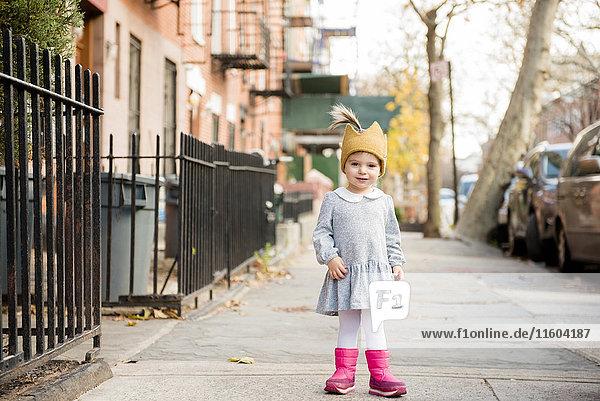 Smiling Caucasian baby girl wearing crown hat on city sidewalk