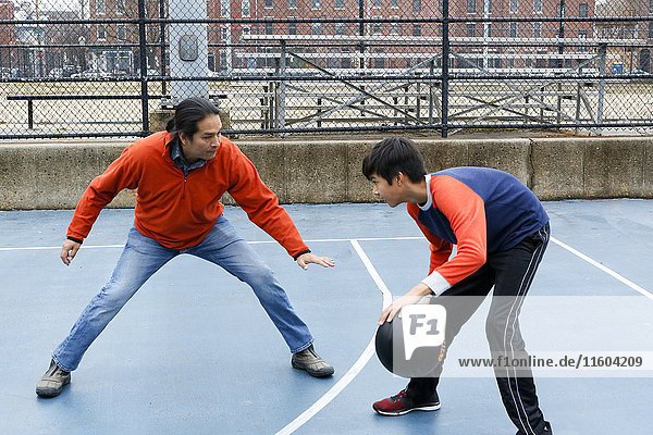 Native American father and son playing basketball