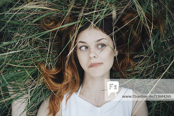 Caucasian woman laying in grass blowing hair off face