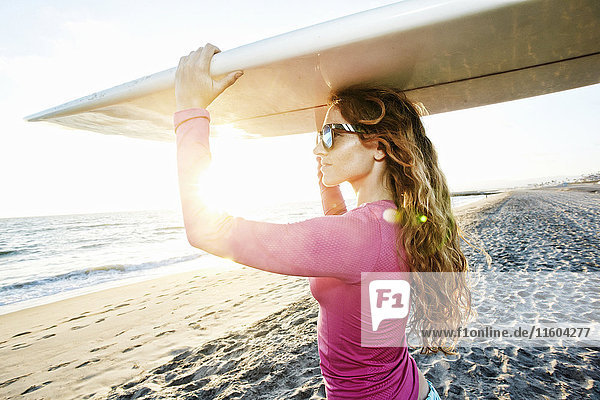 Caucasian woman carrying surfboard on beach Caucasian woman carrying surfboard on beach