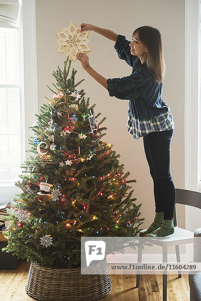 Mixed Race woman placing star ornament on top of Christmas tree