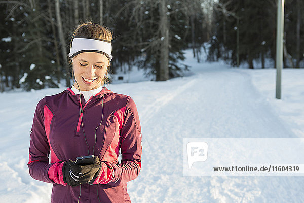 Caucasian runner listening to cell phone with earbuds in winter