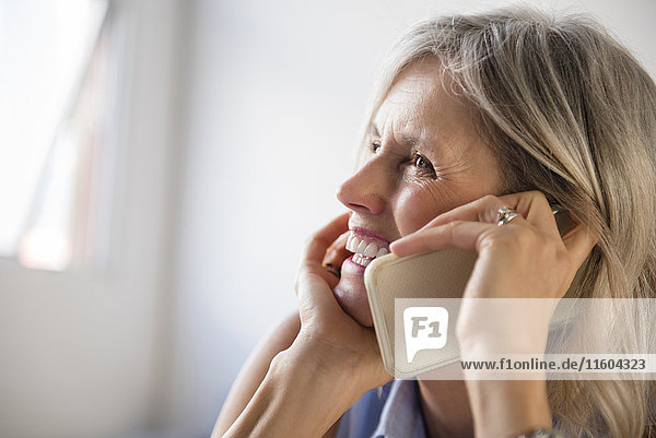 Smiling Caucasian woman talking on cell phone