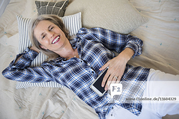 Smiling Caucasian woman laying on bed holding cell phone
