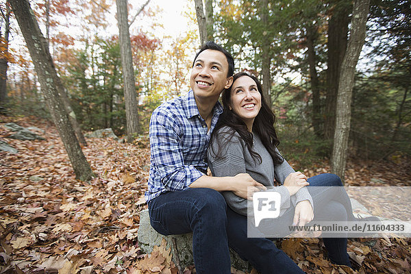 Couple sitting on rock in forest during autumn