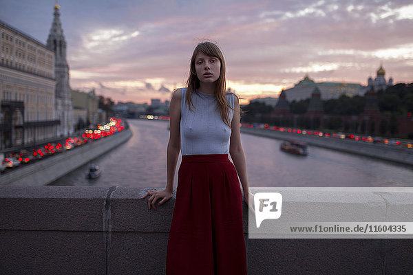 Caucasian woman leaning on bridge over urban canal