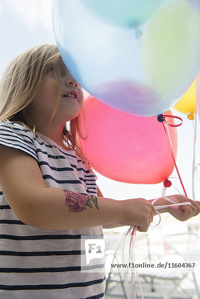 Caucasian girl holding multicolor balloons