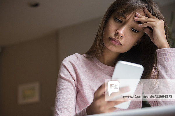 Frustrated Mixed Race woman texting on cell phone