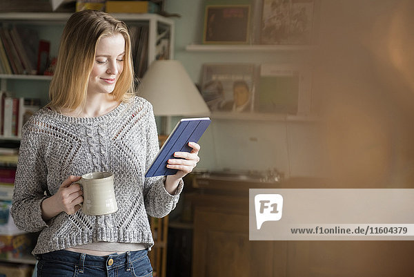 Smiling woman drinking coffee and using digital tablet