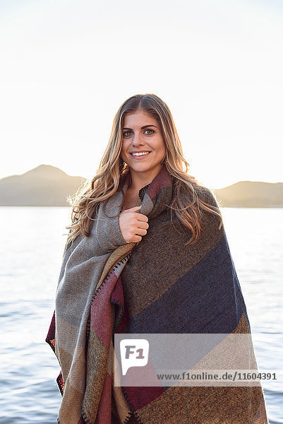 Hispanic woman wrapped in blanket at river