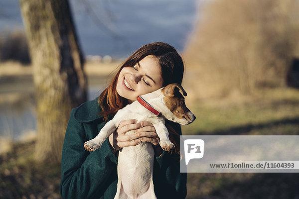 Caucasian woman lifting an hugging dog