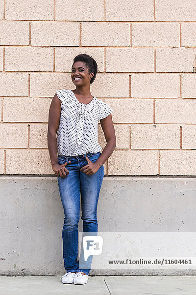 Smiling African American woman posing near concrete wall