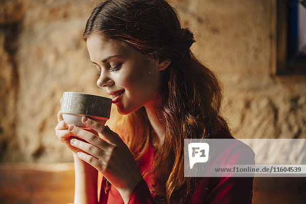 Caucasian woman sipping cup of tea