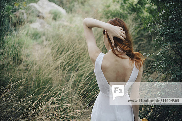 Caucasian woman standing in tall grass with hand in hair