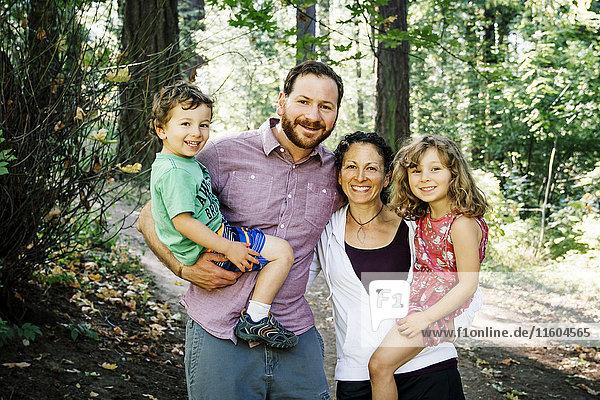Portrait of smiling Caucasian family in park