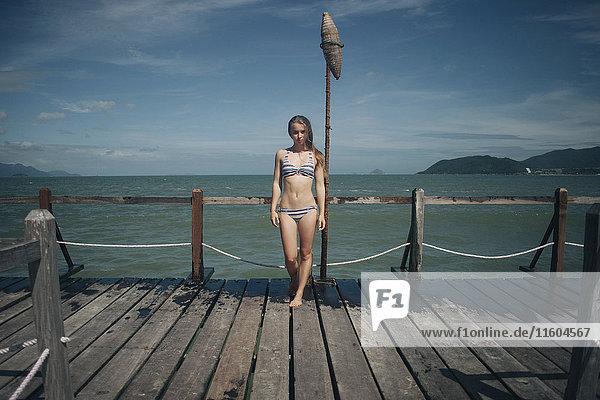 Caucasian woman wearing bikini standing on dock