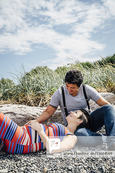 Pregnant lesbian couple relaxing on rocky beach