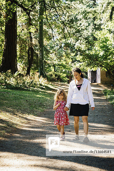 Caucasian mother and daughter walking on path in park