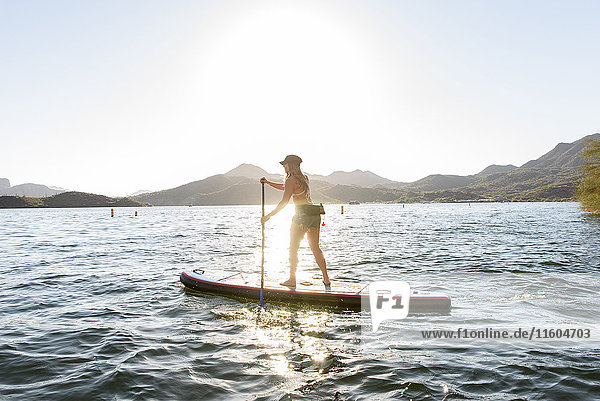 Hispanic woman standing on paddleboard in river