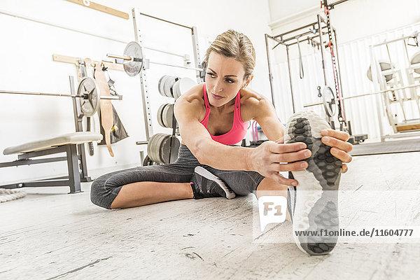 Woman sitting on floor in gymnasium stretching leg