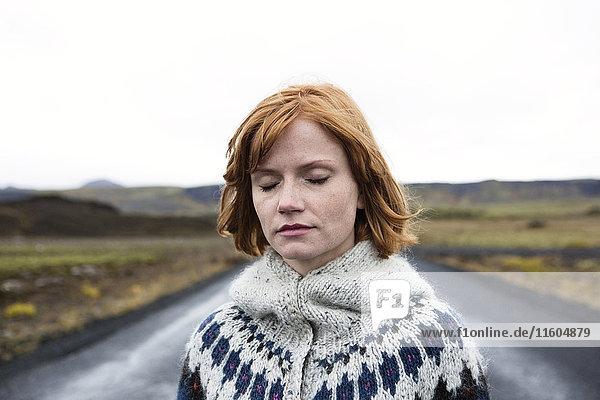 Caucasian woman wearing sweater in road