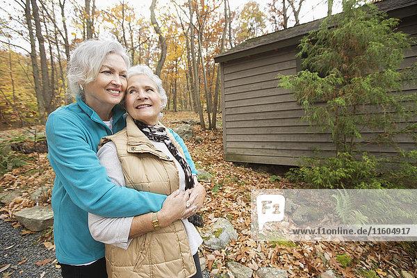 Caucasian women hugging outdoors near cabin