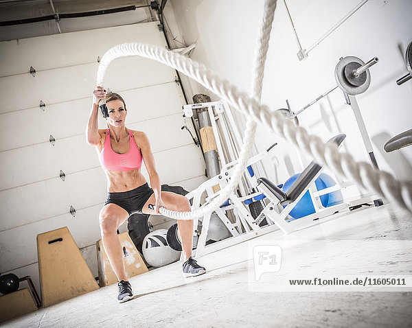 Woman lifting heavy ropes in gymnasium