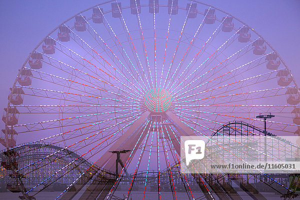 Double exposure of ferris wheel and roller coaster