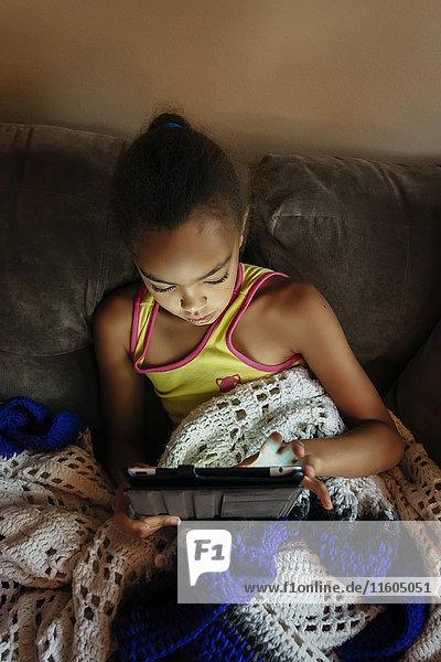 Mixed Race girl using digital tablet on sofa at night
