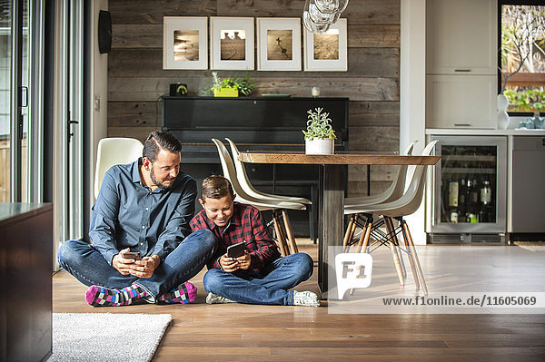 Smiling father and son sitting on floor texting on cell phones